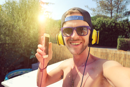 Young man listening to music on a hot summer day