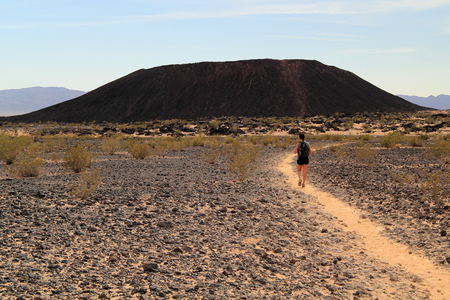 approaches: A female hiker approaches the Amboy Crater in California