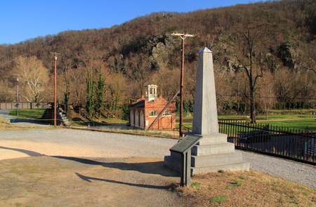 An obelisk marks the original site of John Brown's fort, visible in the background, which played a key role in antebellum U.S. history April 13, 2018 in Harpers Ferry, WV Foto de archivo