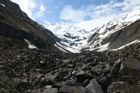 A wide angle shot of the byron glacier and jagged rocky valley below.