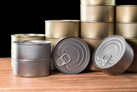 many canned tuna products, gold and silver color on wooden table and black background