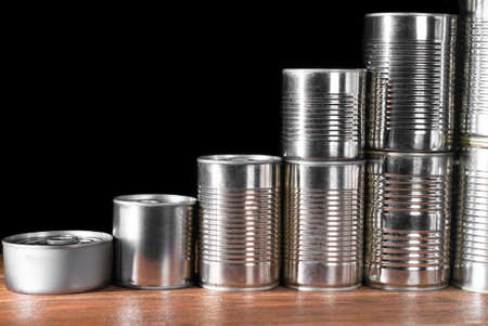 Small and medium canned products in silver pyramid on brown wooden table and dark background