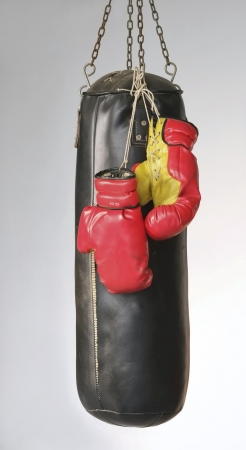 Bokshandschoenen opknoping op zandzak Stockfoto