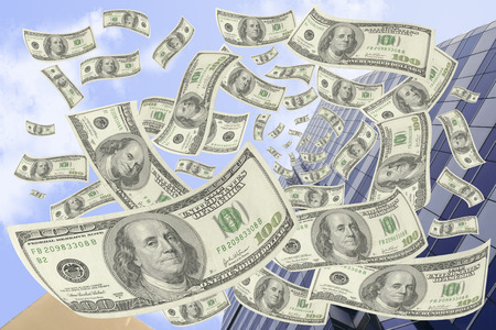 transfer pricing: Hundred-dollar bills falling from the building. Stock Photo