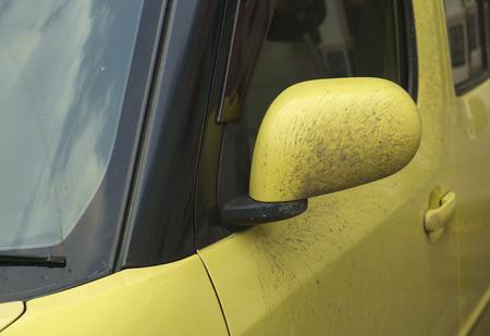 dirty car: Dirty yellow mirror of car.