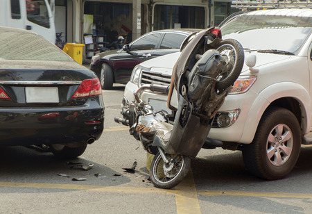 Car and motorcycle collided on the road. Editorial
