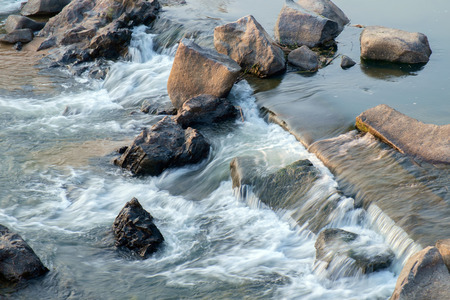 range of motion: Stream flowing water over rock of river.