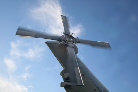 Tail rotor of helicopter on blue sky background.