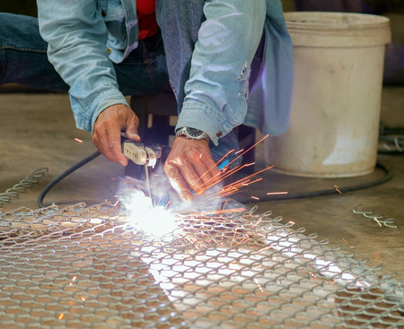 electrode: Welder welding steel mesh by electrode with electric arc. Stock Photo