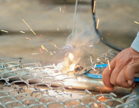 electrode: Close up of welder welding steel mesh by electrode with electric arc. Stock Photo