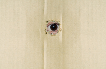 eye hole: Eye looking through hole in brown corrugated paper.