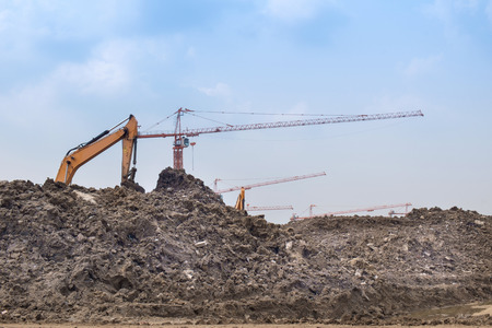 Mound of earth in construction site with blue sky background. Stock Photo