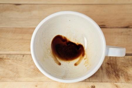 manchas de cafe: Taza de caf� con manchas de caf� no ha lavado la taza colocada en el piso de madera. Vista superior. Foto de archivo