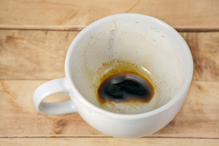 coffee stains: Coffee cup with coffee stains have not washed the cup placed on the wooden floor.