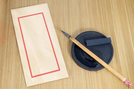 Chinese schrijven penseel en inkt voor kalligrafie en envelop geplaatst op bamboe achtergrond.