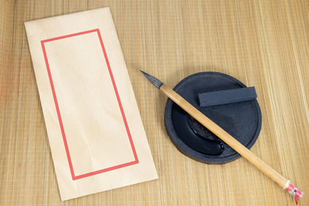 Chinese writing brush and ink for calligraphy and envelope placed on bamboo background. 免版税图像 - 40077387
