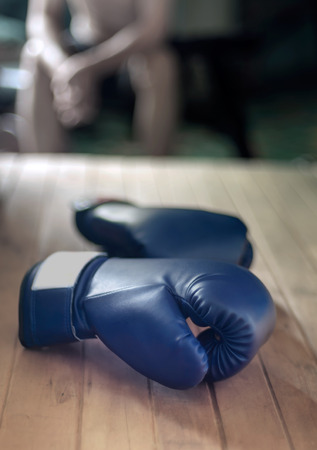 pelea: Boxing gloves on wood and young man sitting on background.