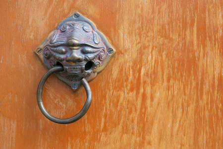 head shape: Old rusty brass doorknob evil head shape on wood door.