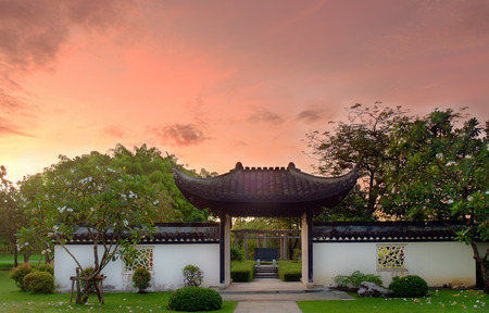 asian gardening: Pavilion of public park chinese style in the morning on orange sky background.