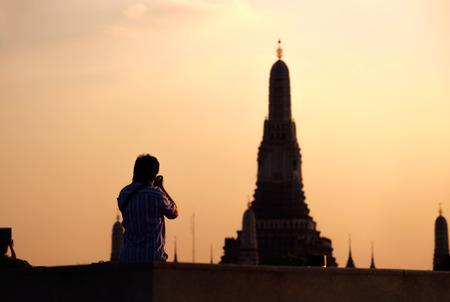 taking photo: Silhouette of photographer taking photo of Wat Arun.
