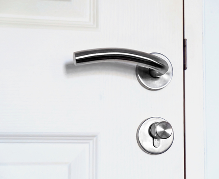 Primo piano maniglia della porta sulla porta bianca.