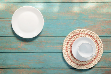 White plate and coffee cup on old wood background. Top view. Flat lay. 免版税图像