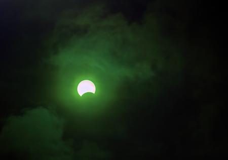 green tone: Partial Solar Eclipse on cloudy. Green tone.