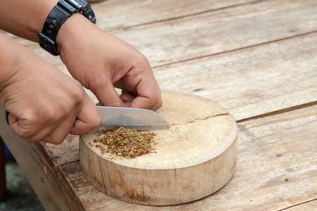 spliff: View of human hand mixing marijuana on wood plate. Stock Photo