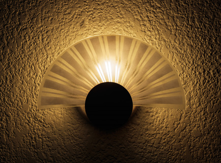 luminance: View of lamp on rough textured wall. Under tungsten light. Dark tone. Stock Photo