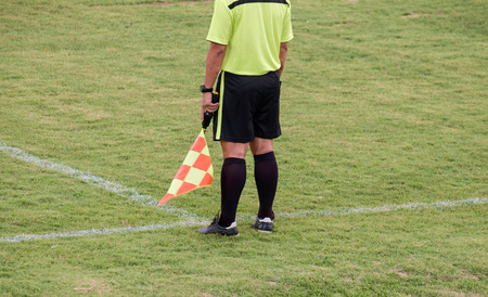 lineman: Lineman, assistant referee of football with flag on sideline. Stock Photo