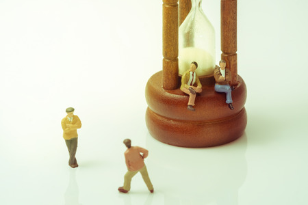 argumentation: View of miniature toy people with vintage hourglass on white background. Vintage style. Stock Photo
