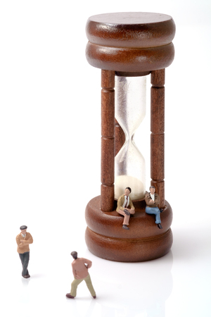 argumentation: View of miniature toy people with vintage hourglass on white background. Stock Photo