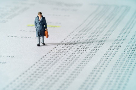 View of miniature toy, businessman walking on financial documents. Soft blue filter. Stock Photo