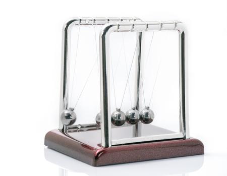 Old momentum pendulum on white background. Stock Photo