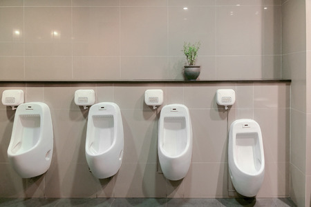 latrine: Empty urinals in public toilet for men only.