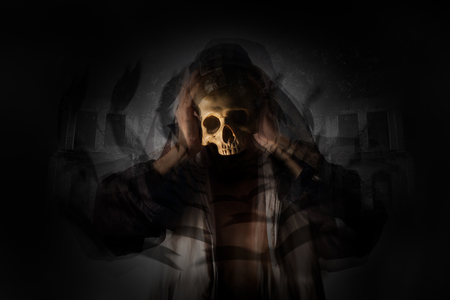 death head holding: Motion man holding skull with blur of flying bat on old building background. Dark tone. Stock Photo