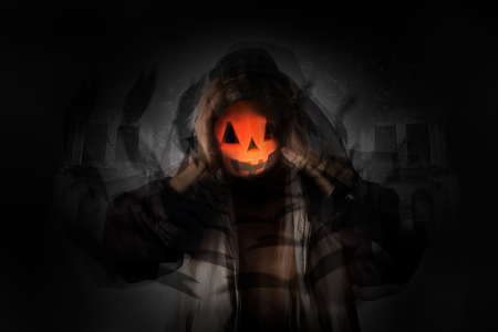 death head holding: Motion man holding pumpkin head with blur of flying bat on old building background. Dark tone.