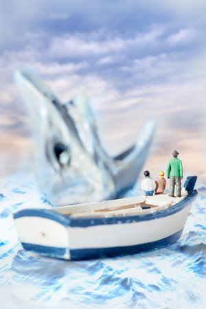 model fish: View of miniature toy, young man and girl sit on boat looking shark.