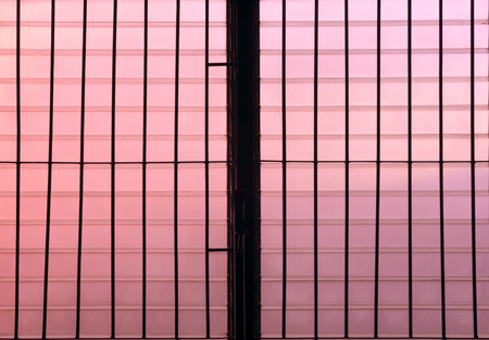 louver: Silhouette of dirty louver window at twilight. Pink tone.