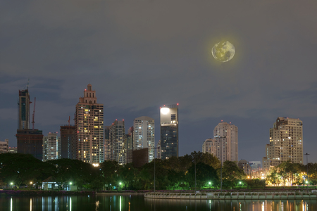 View of city at night with moon. Stock Photo