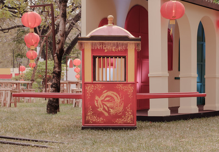 View of traditional Chinese sedan chair on the ground.