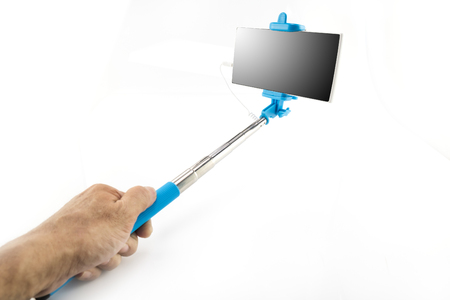 Hand holding selfie monopod stick with mobile phone on white background. Stock Photo
