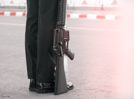 View of soldier standing with gun on street. Stock Photo