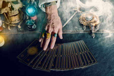 Hand van waarzegster en tarotkaart op de tafel bij kaarslicht. Donkere toon. Stockfoto