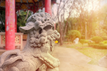 Statue of chinese lion in park with sunlight. Stock Photo
