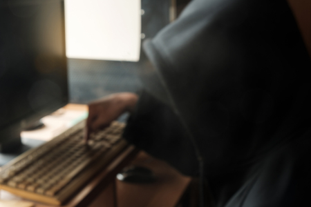 Blur of hooded man using computer.