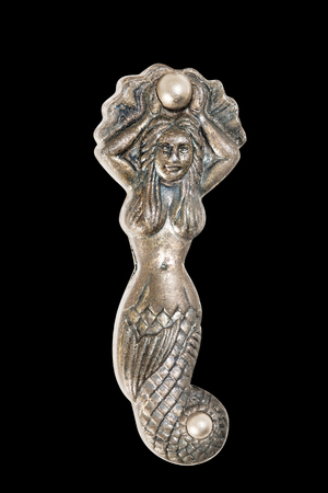 Mermaid on black background, made from brass. Stock Photo