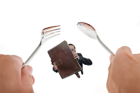 Hands holding spoon and fork with businessman holding old business suitcase on white background.