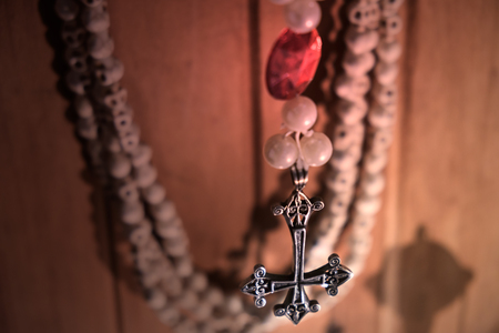 View of crucifix hang on wood wall. Soft focus. Dark tone.