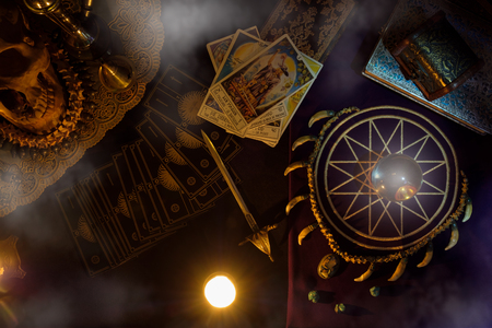 View of crystal ball and tarot card with smoke on the table. Dark tone. Under candlelight. Foto de archivo